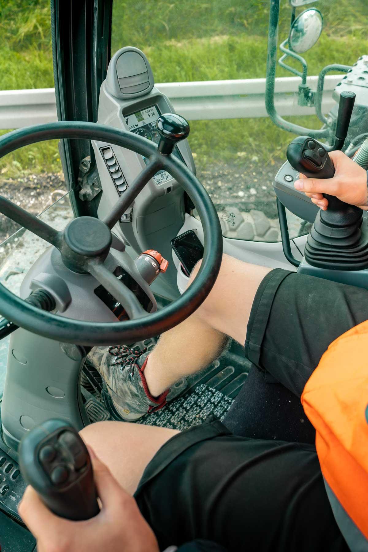 Baggerfahrer mit orangener Jacke am Steuer