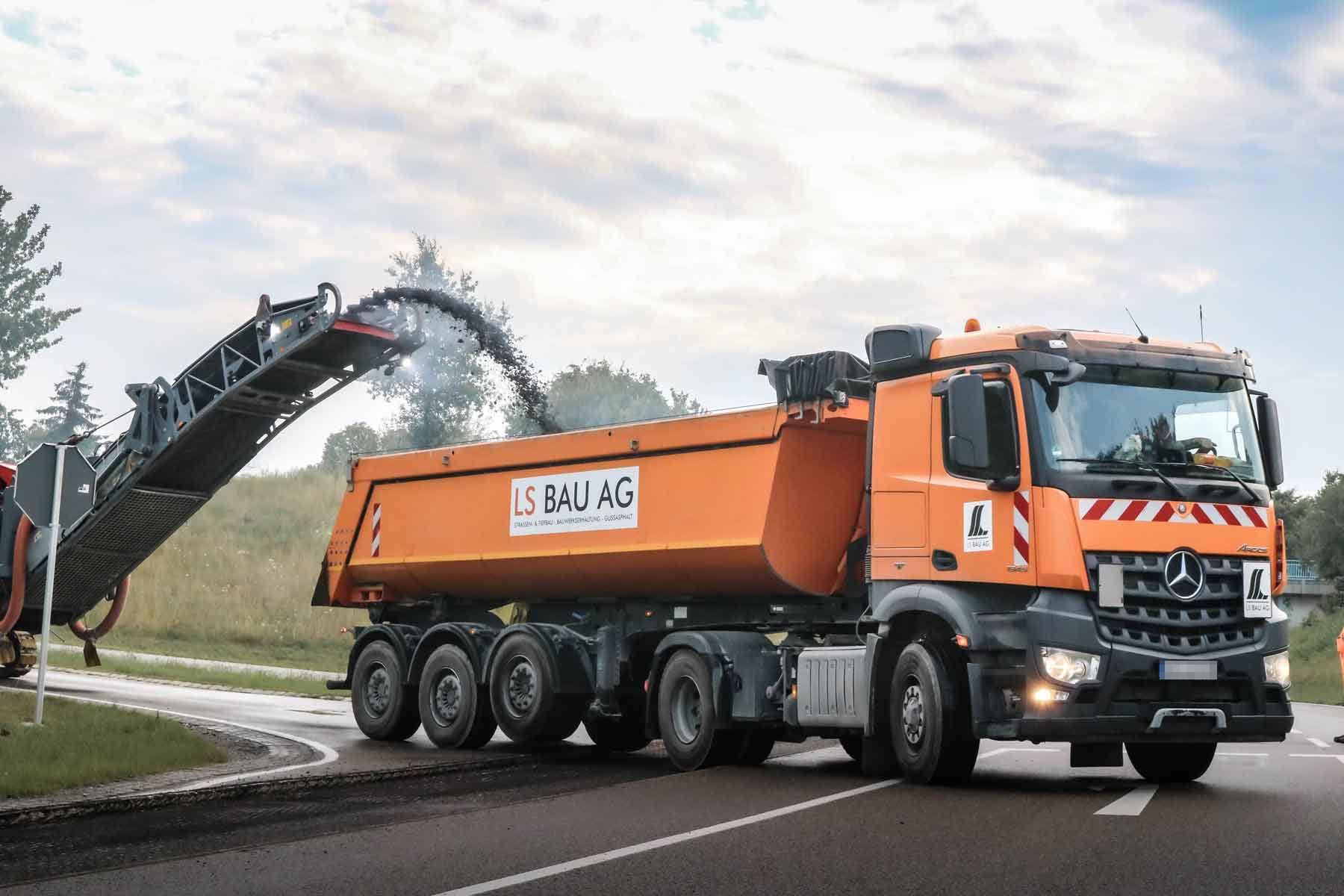 Orangener LKW bei Straßenerneuerung