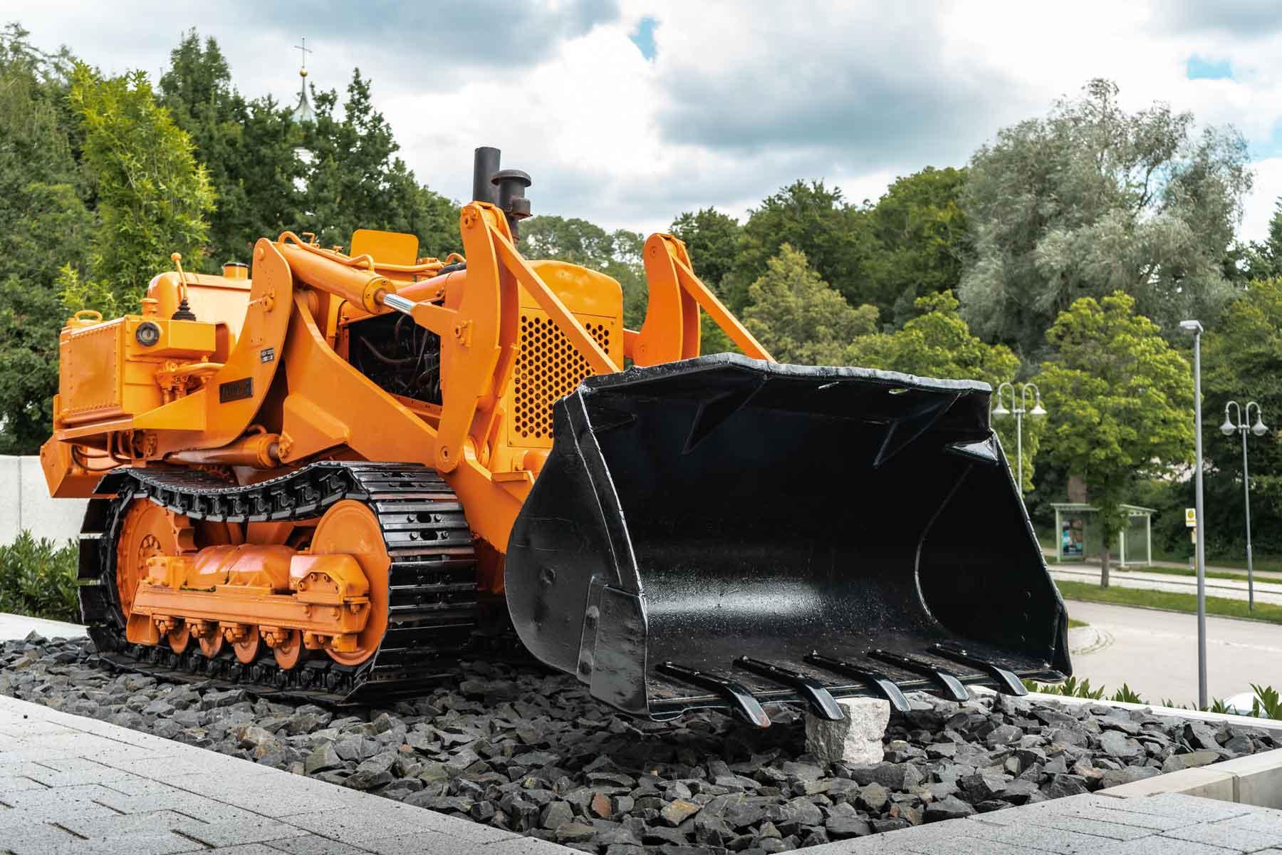 Alte Raupe der LS Bau AG in orange