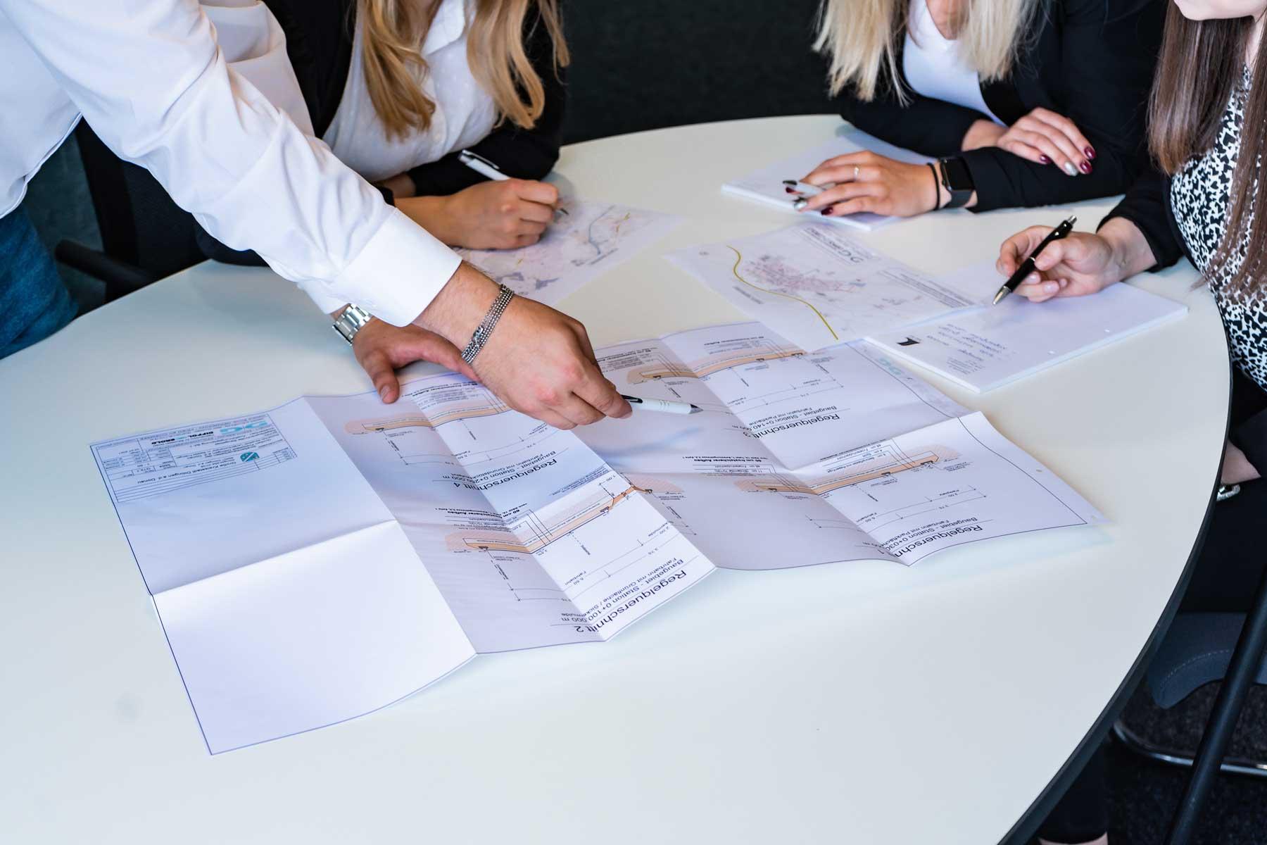 Teambesprechung am Tisch mit Bauplan