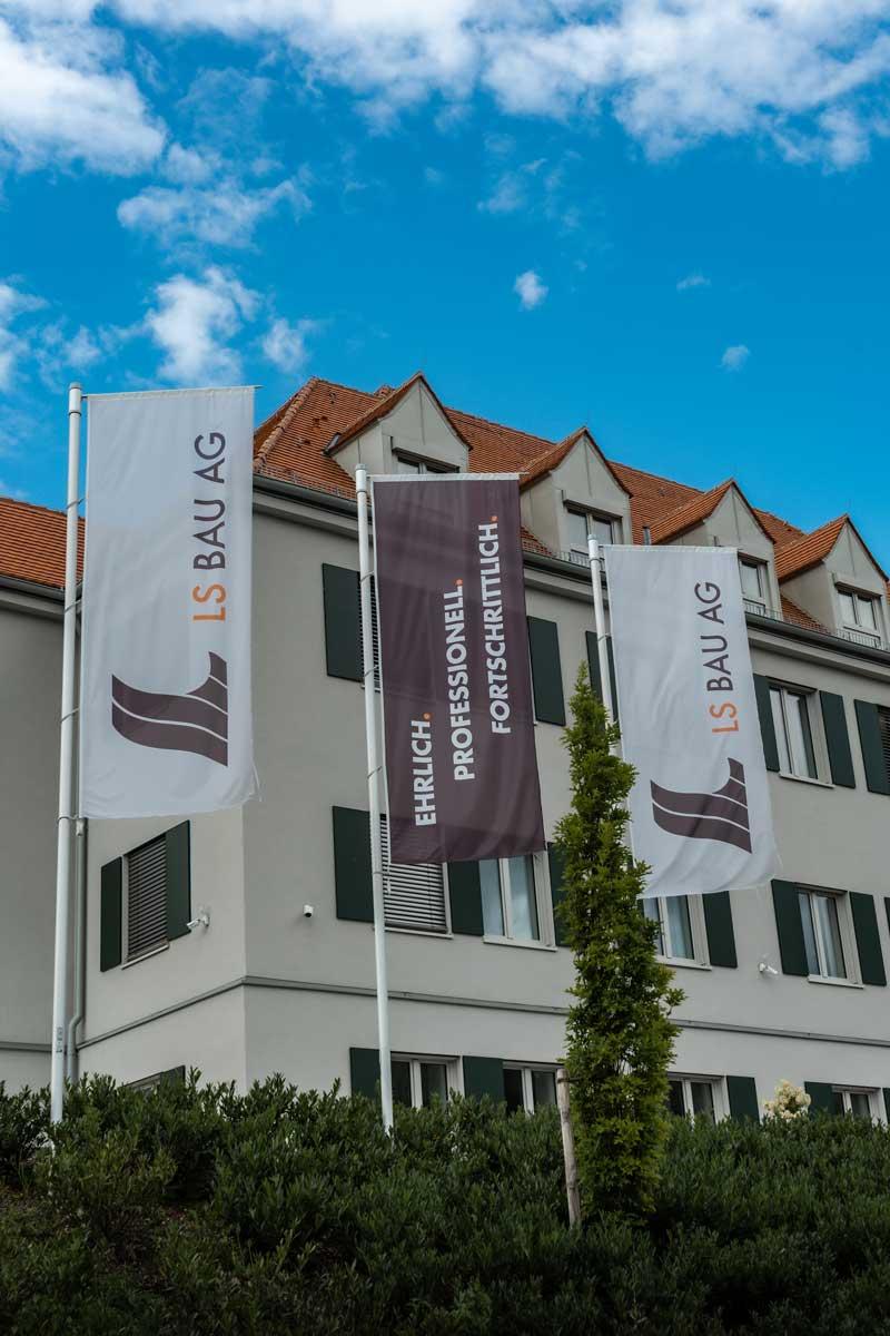 Geschäftsgebäude mit drei Flaggen der LS Bau AG