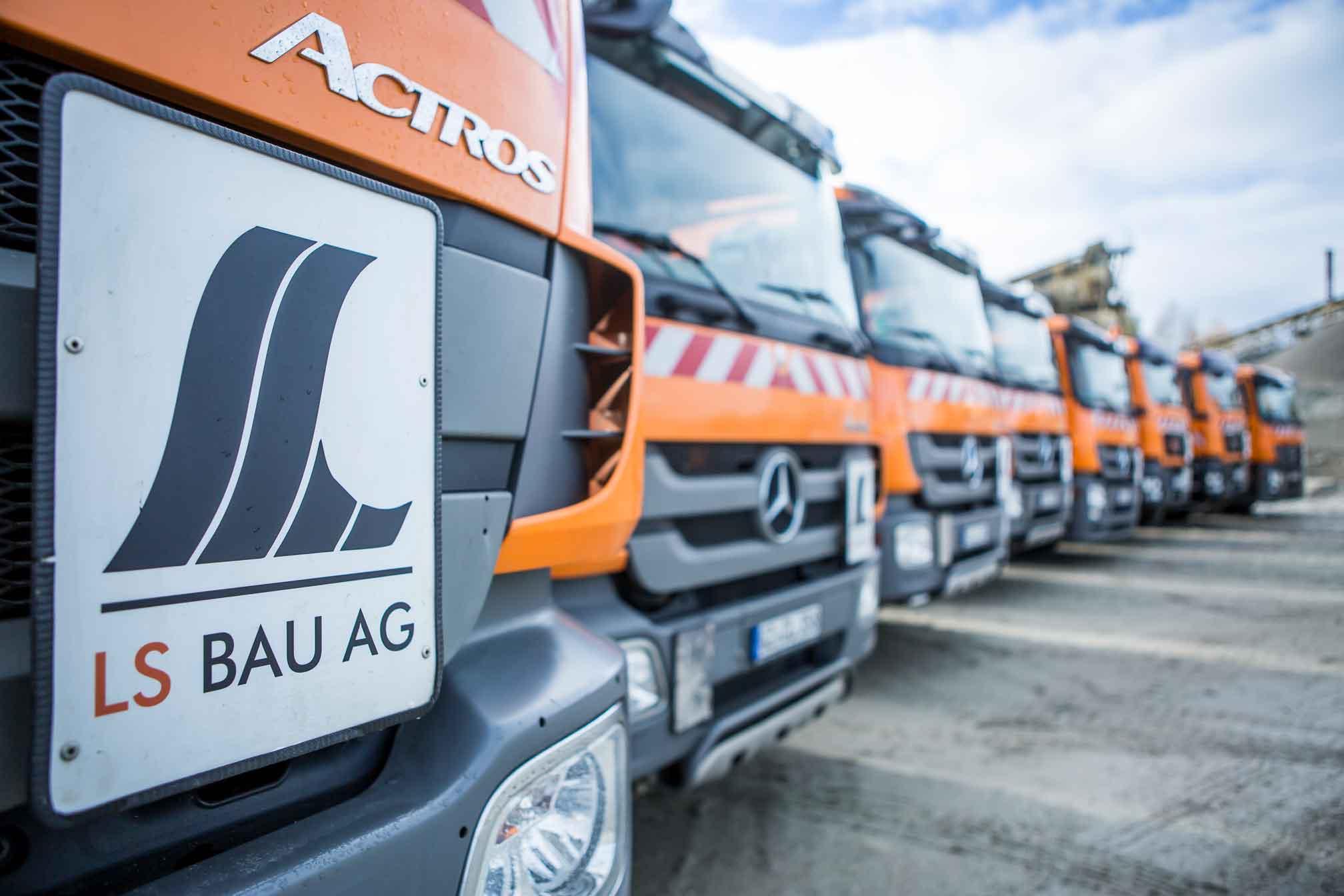 Mehrere LKW'S mit LS Bau AG Logo im Vordergrund