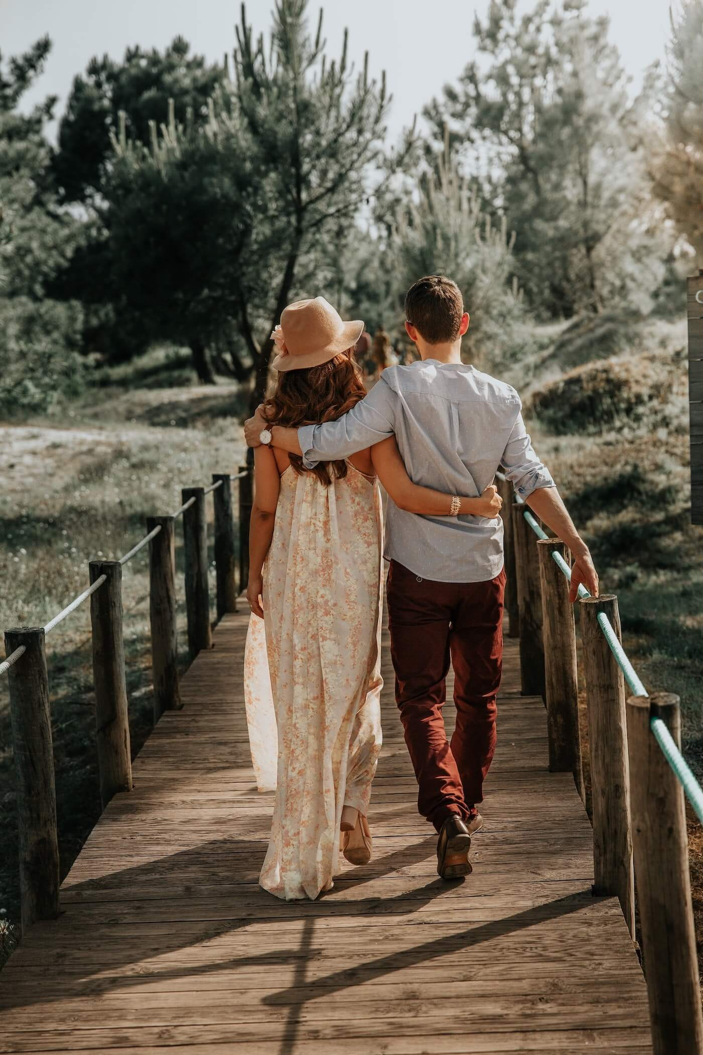 A couple walks down a bridge together for their wedding video