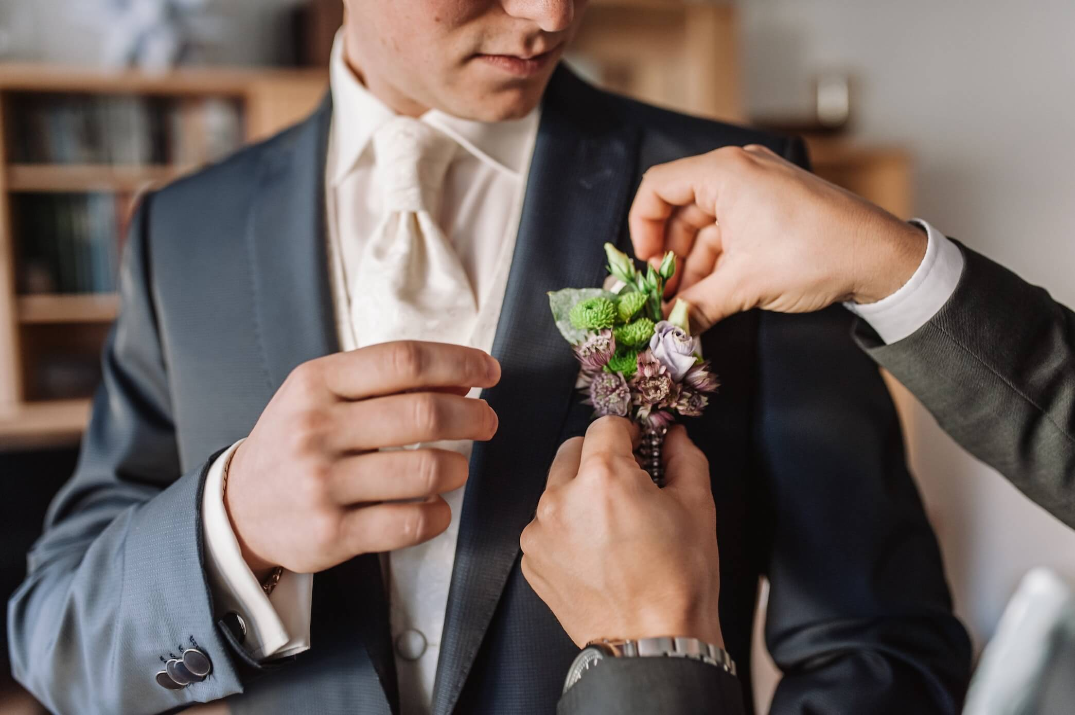 A groom has his boutonnière placed by his best man.