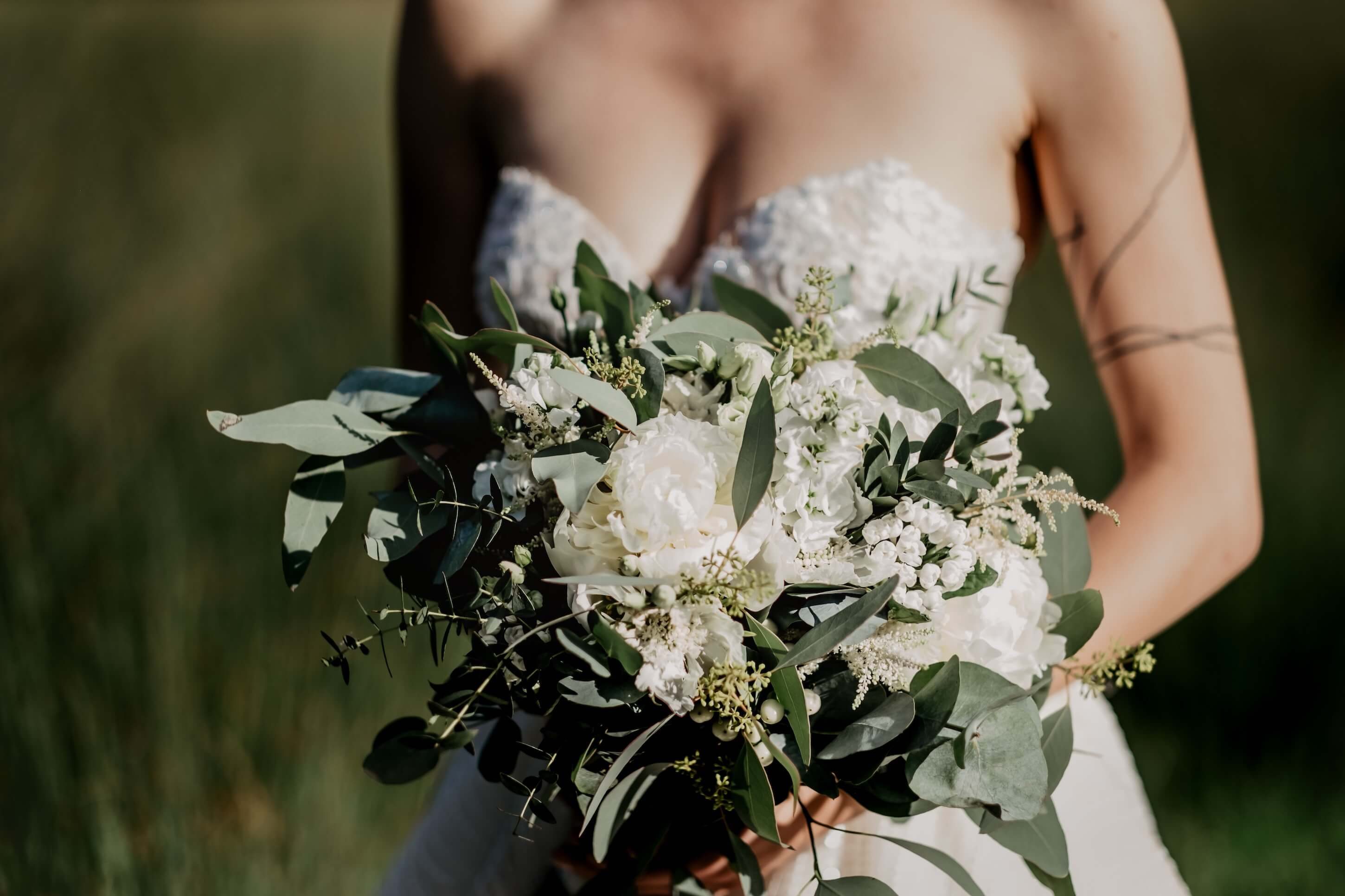 A bride holds her flowers as she walks down the aisle