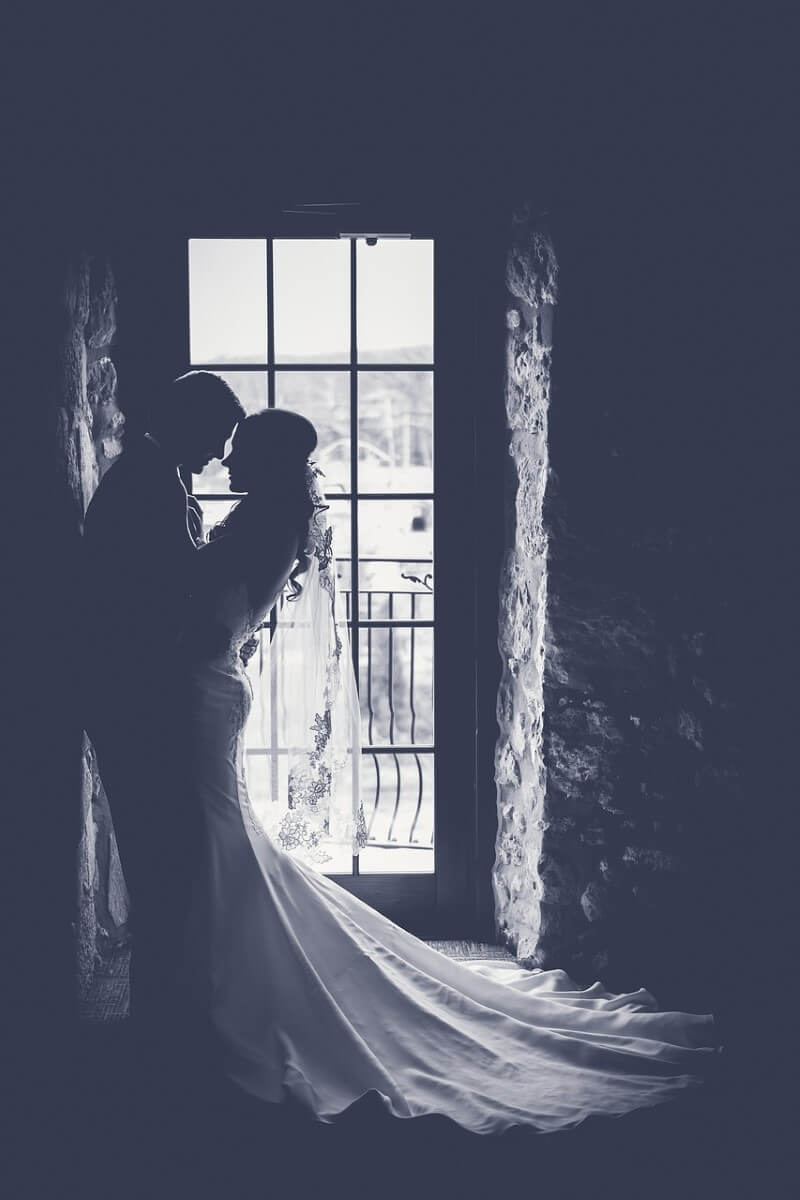 Bride and Groom Holding each other in front of window for Videography