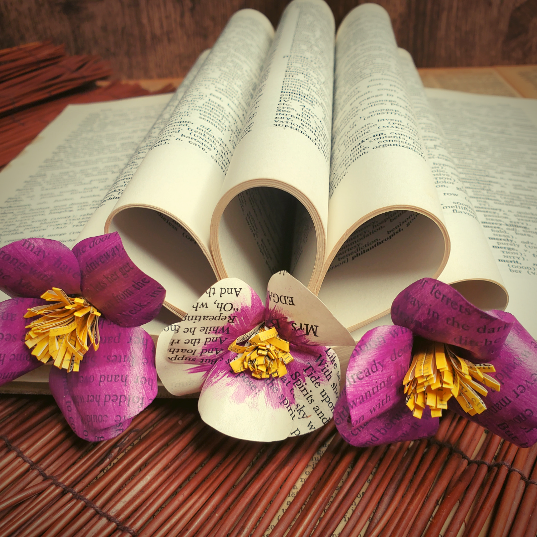 A folded book art display with three book page paper violets.