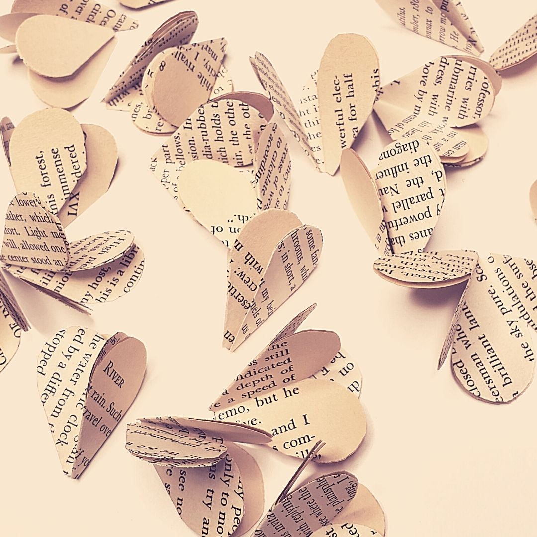scattered book pages cut into little folded hearts or petals