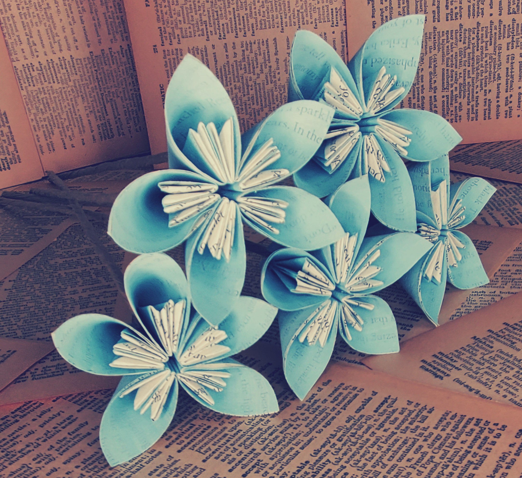 five kusudama flowers in a light teal stacked on each other