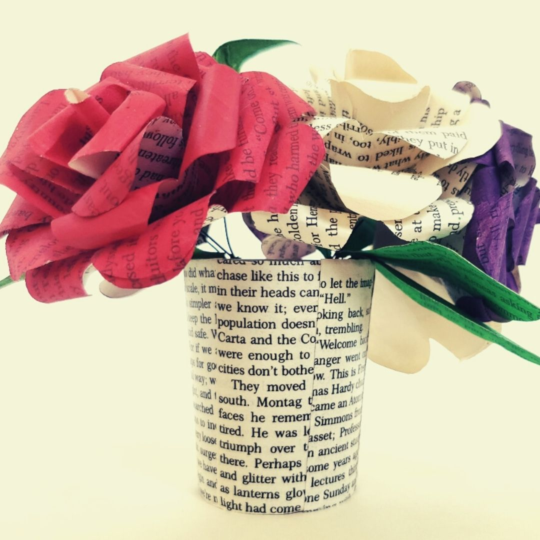 Three book page flowers in a glass vase covered in book pages. The flowers are red, plain, and purple with green leaves.