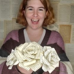 Creator Micaela Lumpkins with three book page flowers smiling