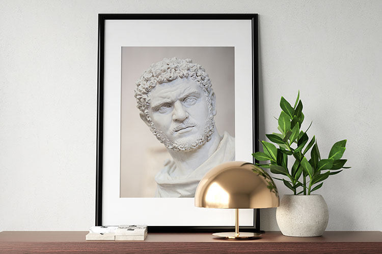 A framed photograph of Roman emperor, Caracalla, formally known as Marcus Aurelius Antoninus on a staged desk.