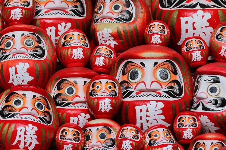 A pile of red Japanese daruma dolls.