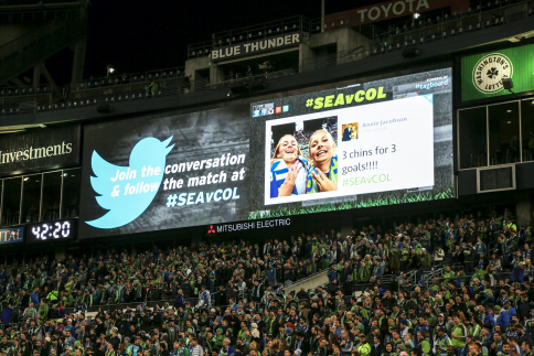 A photo of a crowd of people in a stadium with a large screen above them showing a social media post.