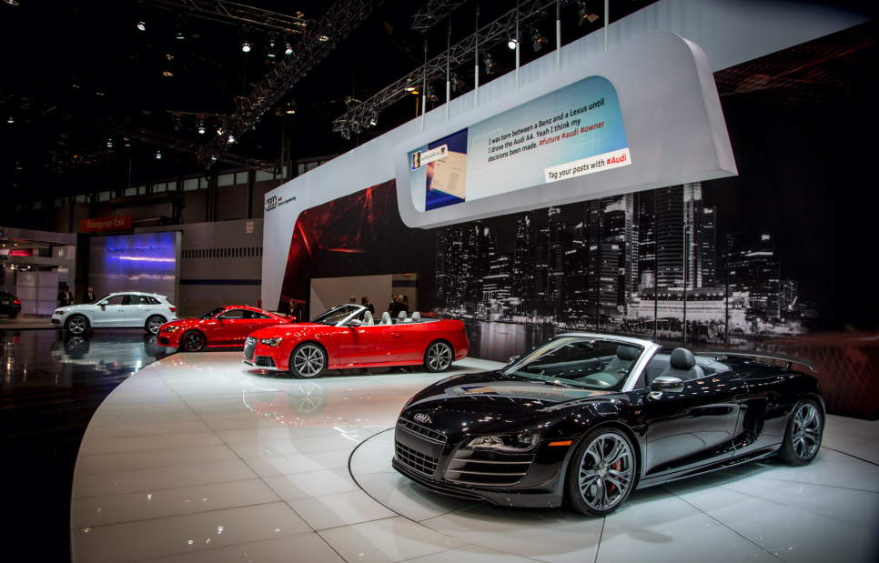 A photo of exotic Audi cars at an auto show with a large, landscape display hanging overhead. On the display is a social media post.