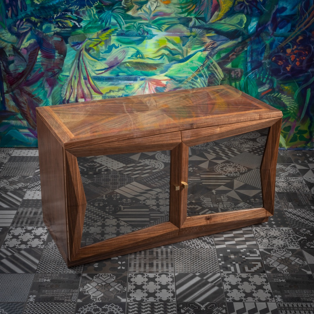 The Cubist cabinet with a glass door is inspired by Pavel Janák's library designed in 1913. For carpenters, it is always a challenge to put the angles on the veneered elements into an appropriate figure. When all goes well, the sight of such a piece of furniture is uplifting. Glass fillings have a partially mirror effect. We can make a cabinet to order from any available veneer. It can also be ordered in sets of two or more pieces.
