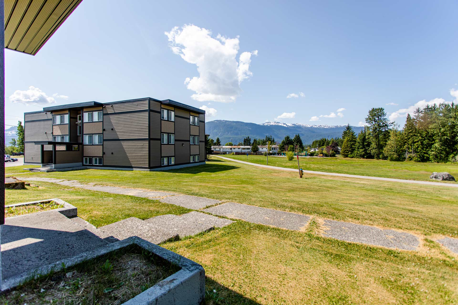 Green space around Hillcrest Place Apartments in Kitimat, B.C., with apartment building on the left.