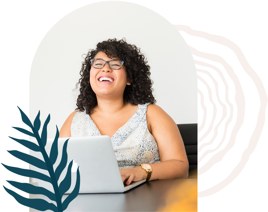 A feminine presenting Black person laughing while on a computer. Fern leaf and tree trunk vectors.