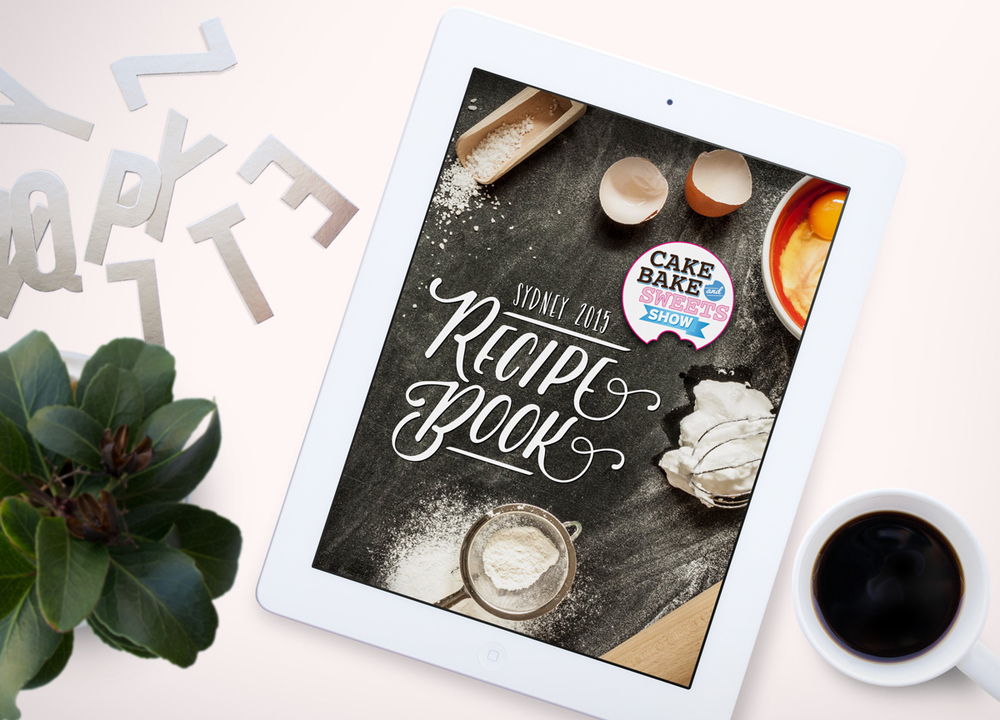 eBook cover for the Cake Bake & Sweets Show digital recipe book. The cover features a kitchen bench with baking ingredients laid out.