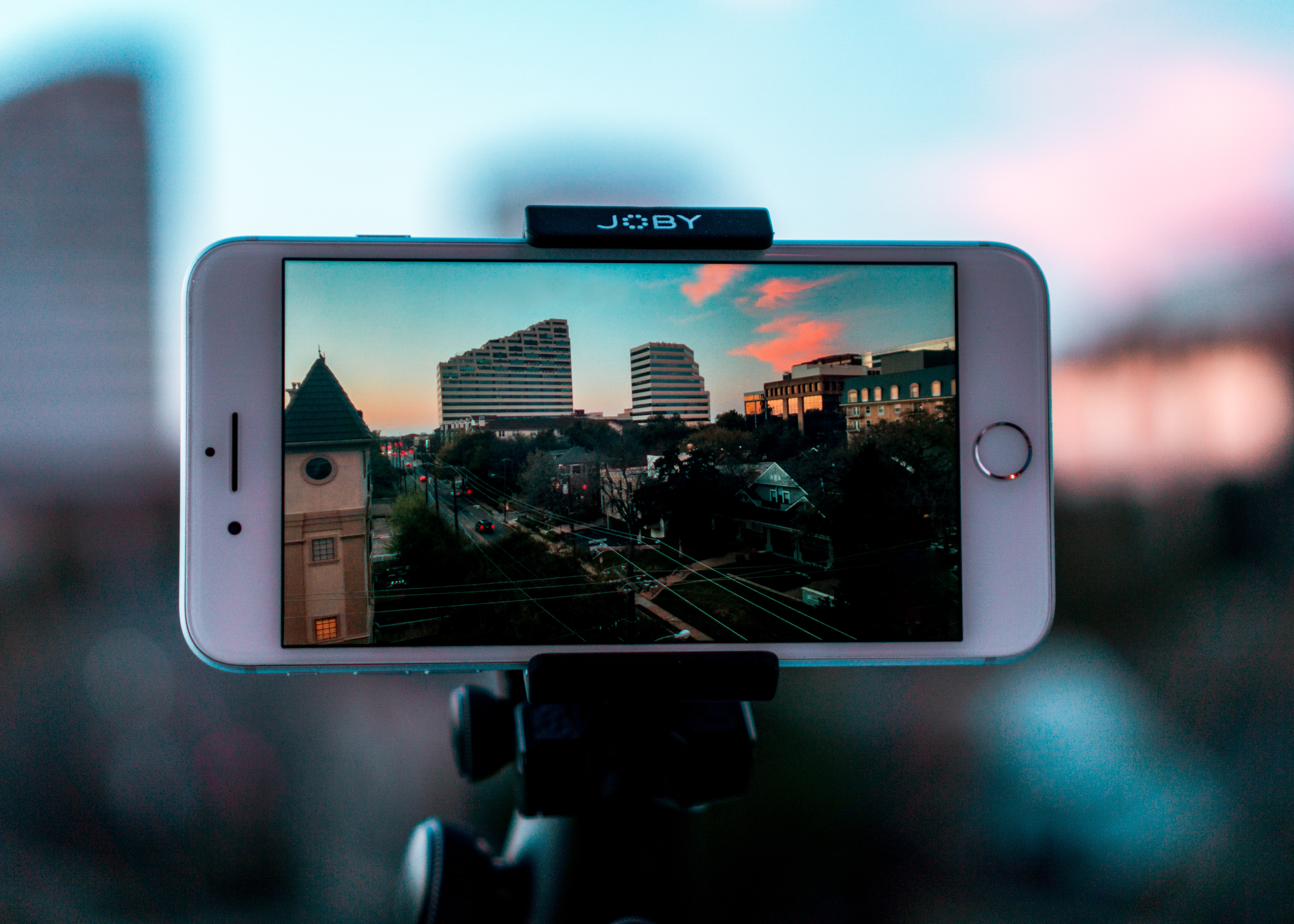 A phone on tripod taking a picture outside the window