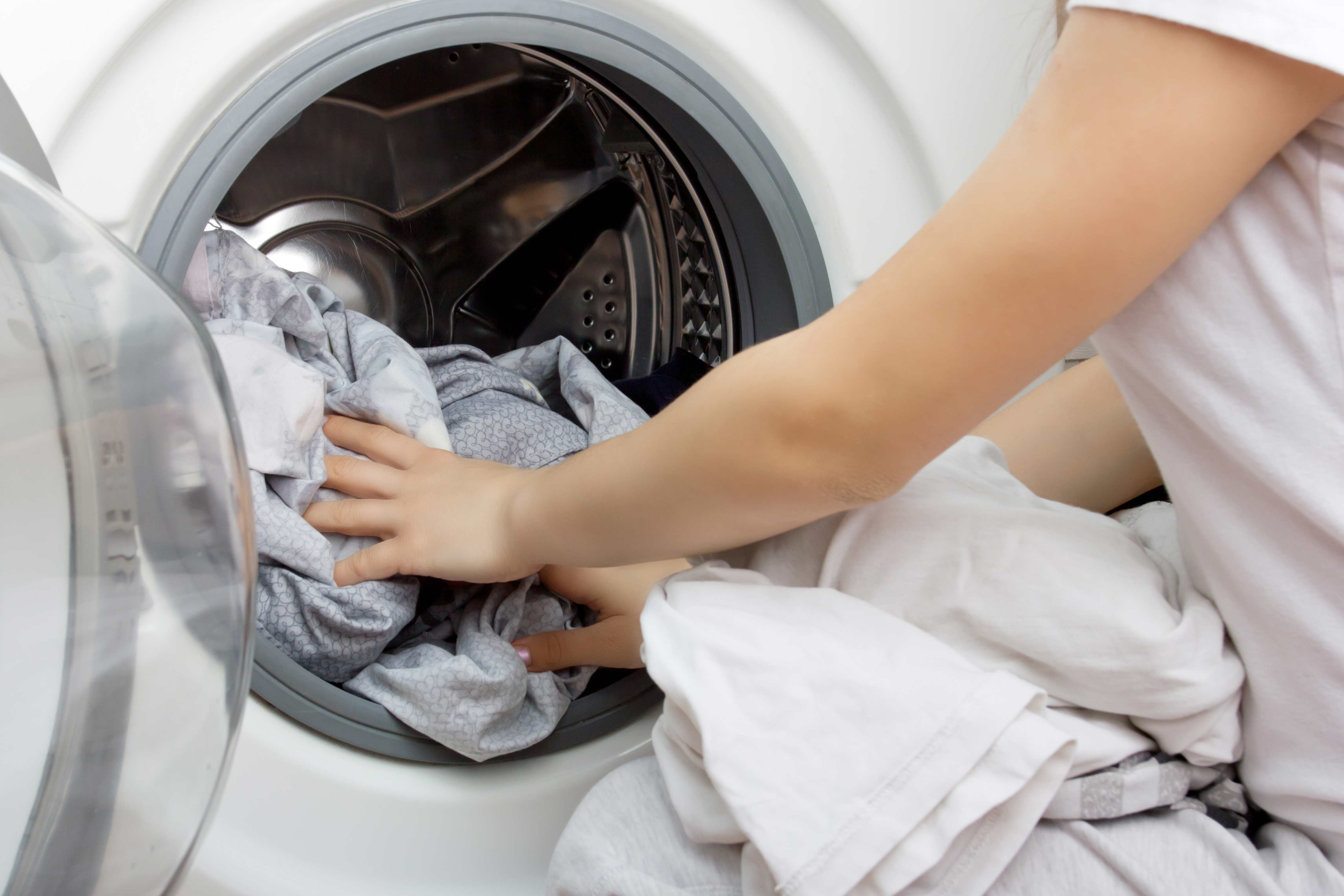 Nainen täyttää pesukonetta