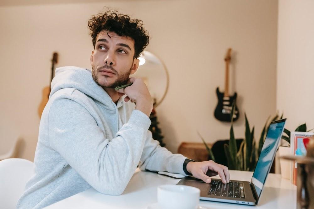 Man sitting at laptop and thinking