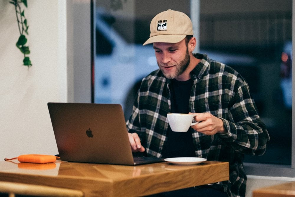 Young entrepreneur working on laptop in coffee shop