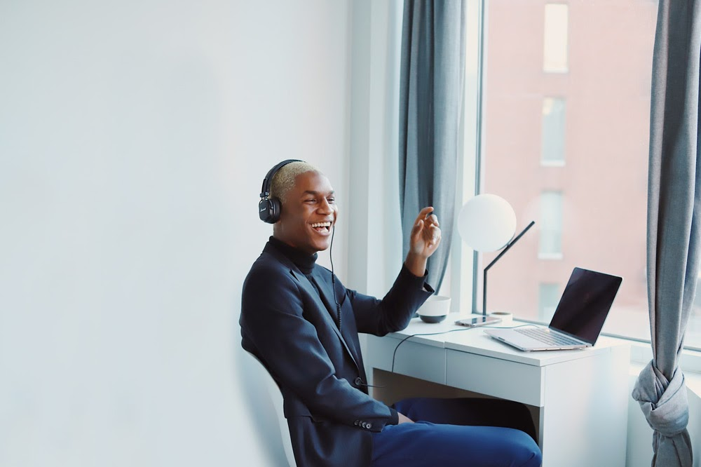 Man sitting at desk listening to music on headphones