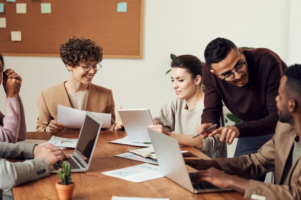 Team of people working around a desk