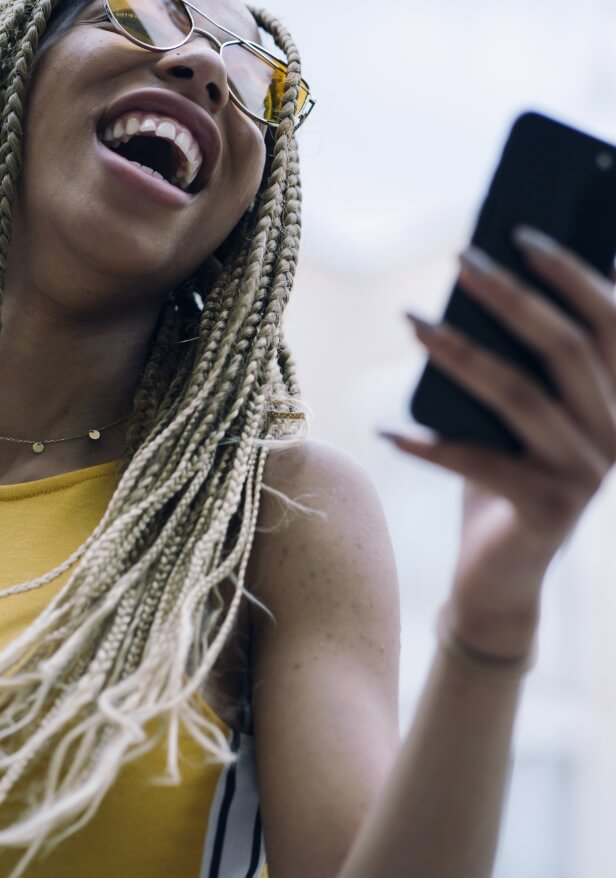 Lady smiles while looking at  her phone