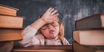 Do I need a solicitor when buying a house at auction: Image of a frustrated tired kid with a pile of books
