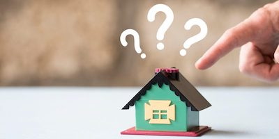 Do houses sell for less at auction? Image of a model house with question marks