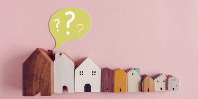 Image of model houses with a question mark above them