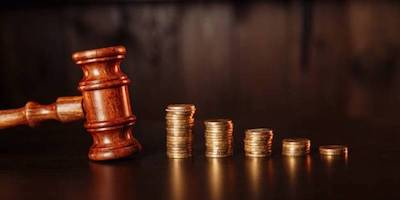 Image of an auction gavel with coins.