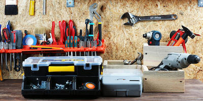Image of a toolbox and other tools. Should you roll your sleeves up and prepare your home for sale by auction, or sell as-is?