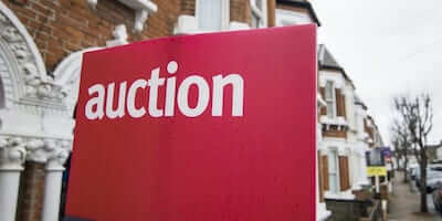 """Image of an auction """"for sale"""" board outside a property"""