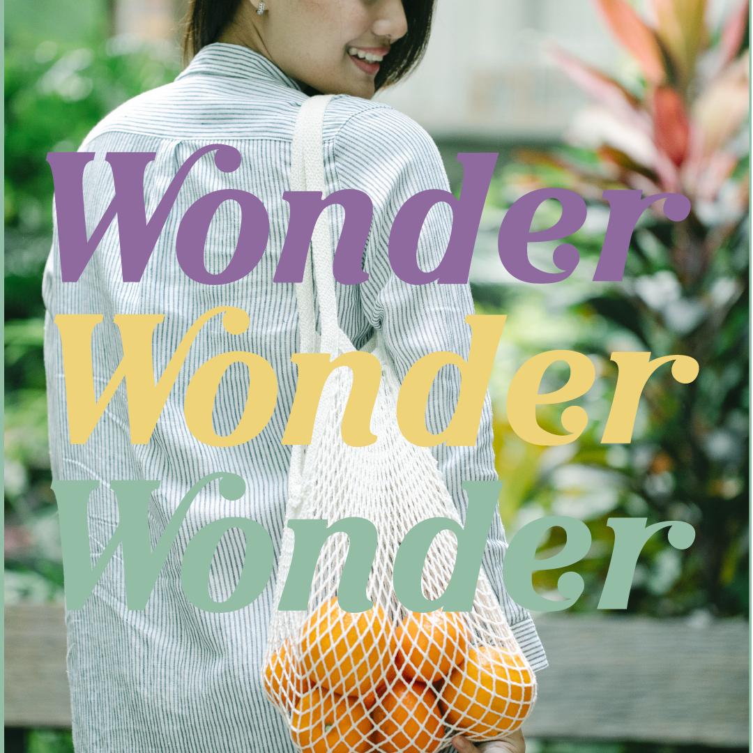Women holding oranges with wonder logo layered ontop