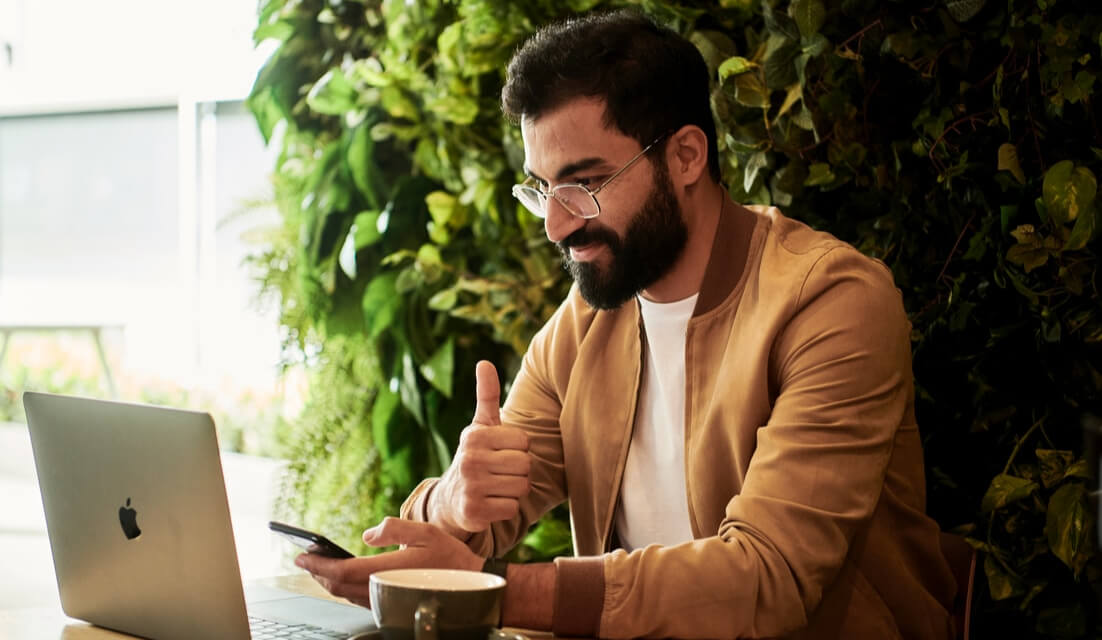 smiling man with thumb up having a call on his laptop