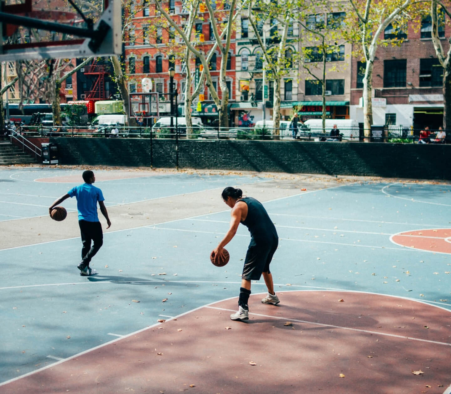 a neighbourhoods basketball court with two people playing
