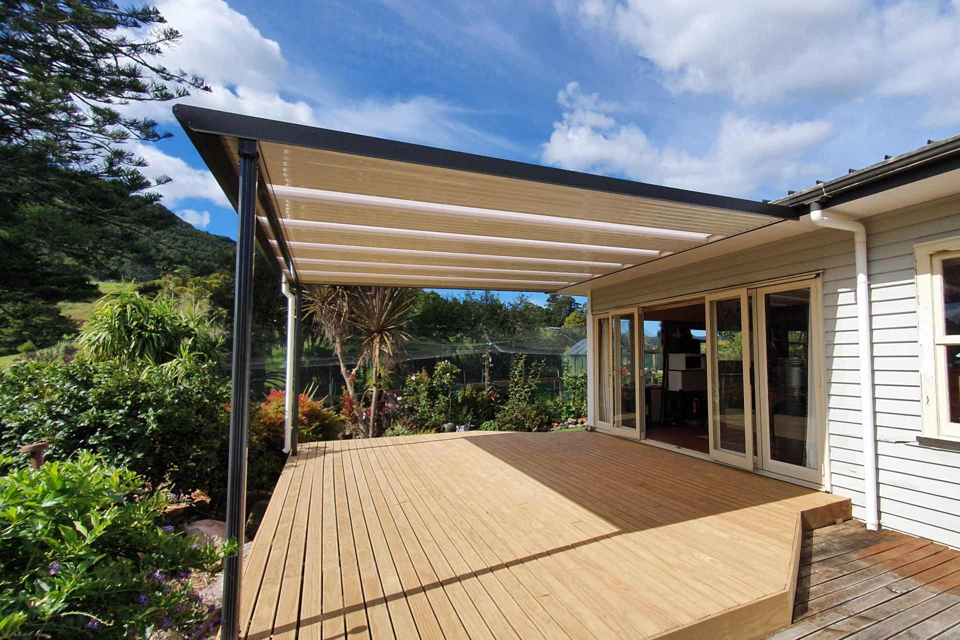 An outdoor deck is covered with a flat roof to enable use all year round