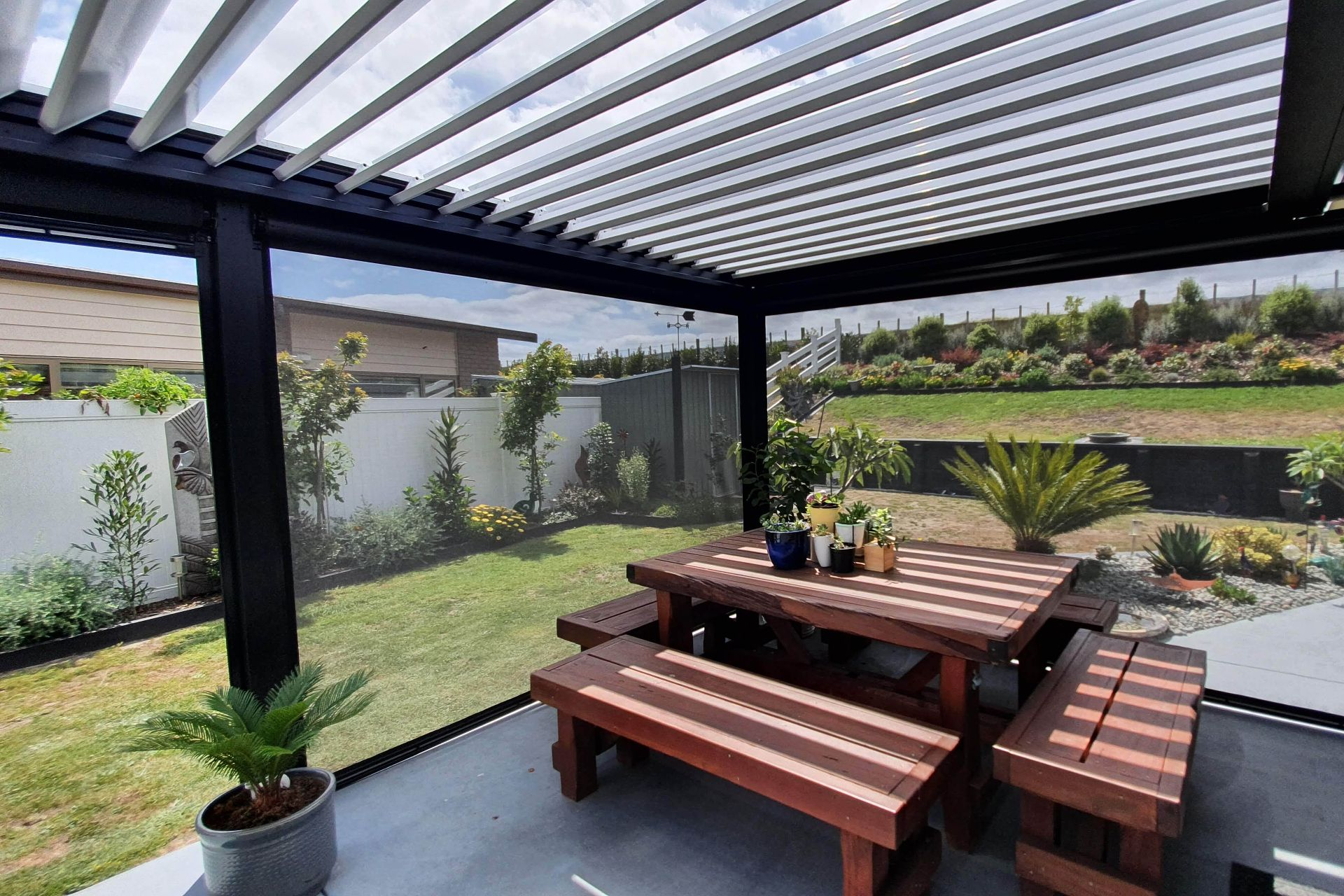 An outdoor patio area with table and chairs is covered with a black louvre roof and enclosed with outdoor blinds