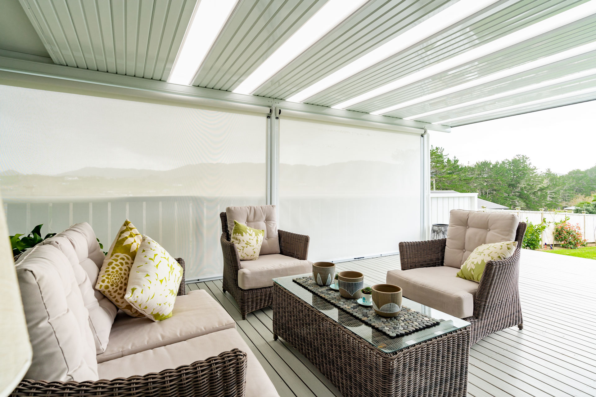 An outdoor deck area with table and chairs is covered by a flat roof and enclosed with outdoor blinds