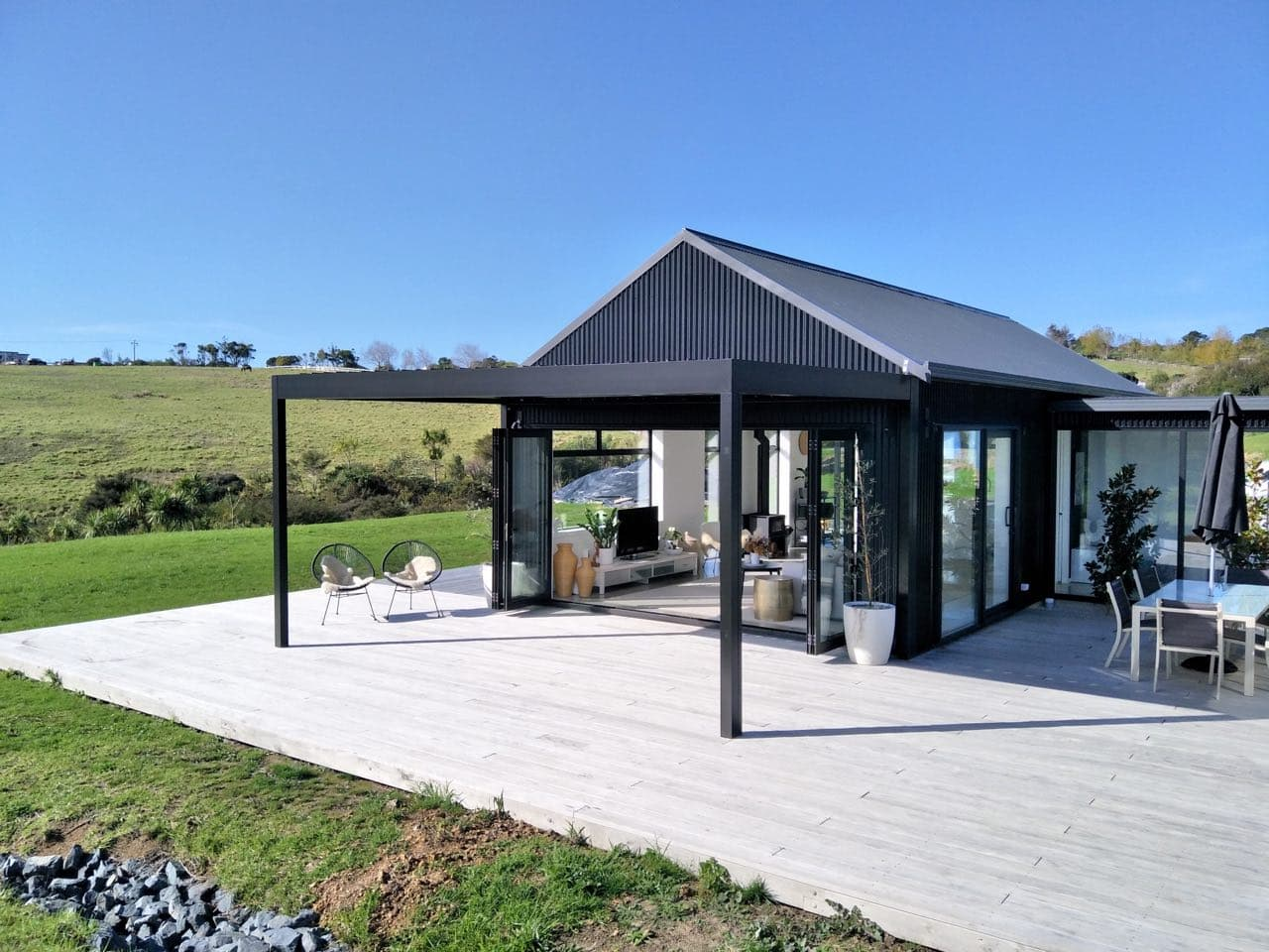 Black louvre against black gable end covering deck area with outdoor seats