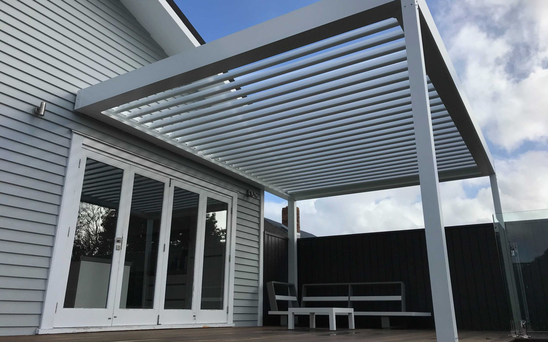 white louvre over deck to provide shelter for outdoor lounge suite