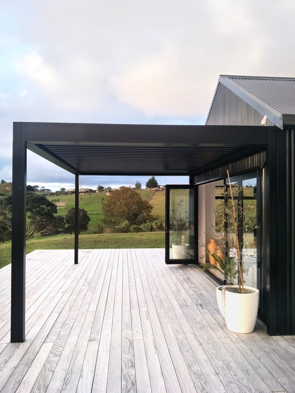 Black louvre against black house covering deck