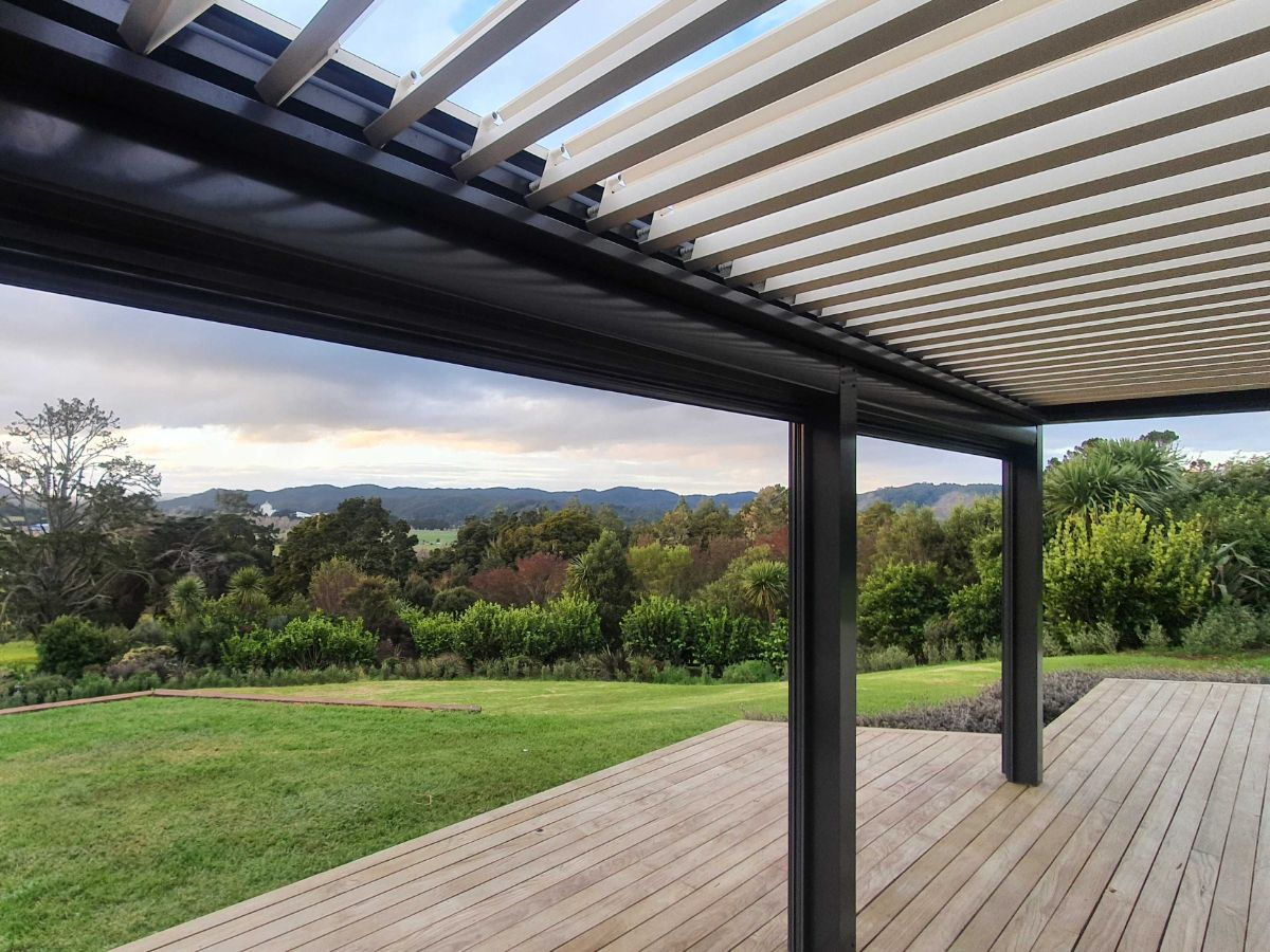 Beautiful view from under a louvre roof out toward the country side. Louvre blades are open, allowing the sun and breeze to fill the space
