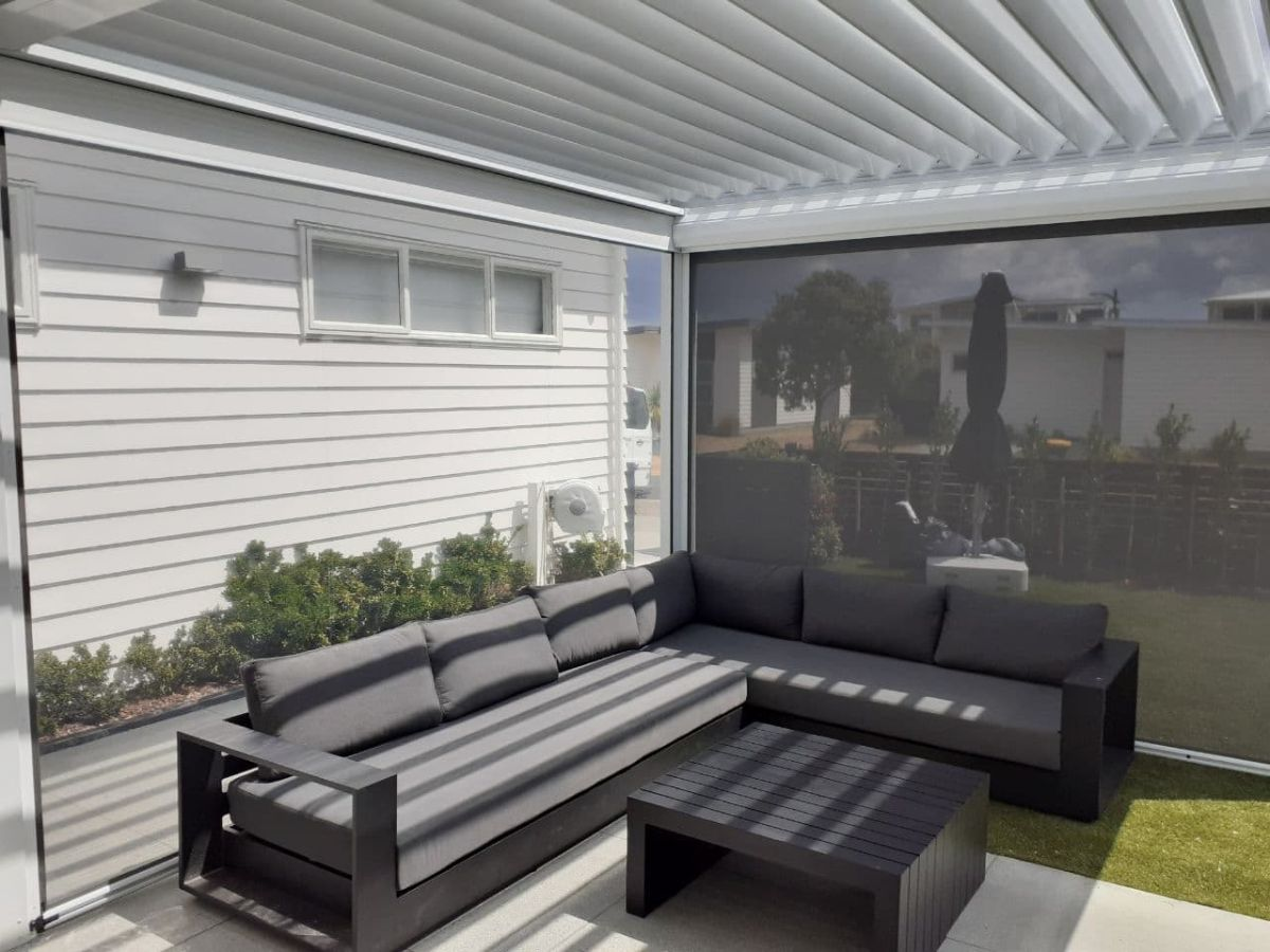 Mesh and PVC blinds enclosing white louvre roof over lounge furniture
