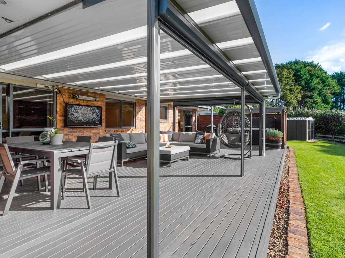 Flat roof and blinds covering large decked area with tables, chairs and lounge suite