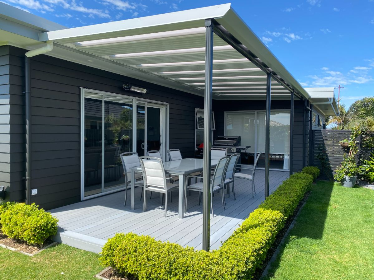Flat roof covering bbq, table and chairs in L-shape deck area surrounded by hedge