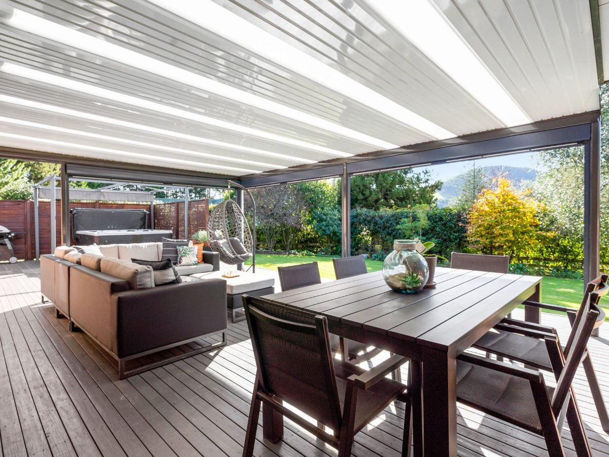 Outdoor lounge and dining on deck covered by flat roof